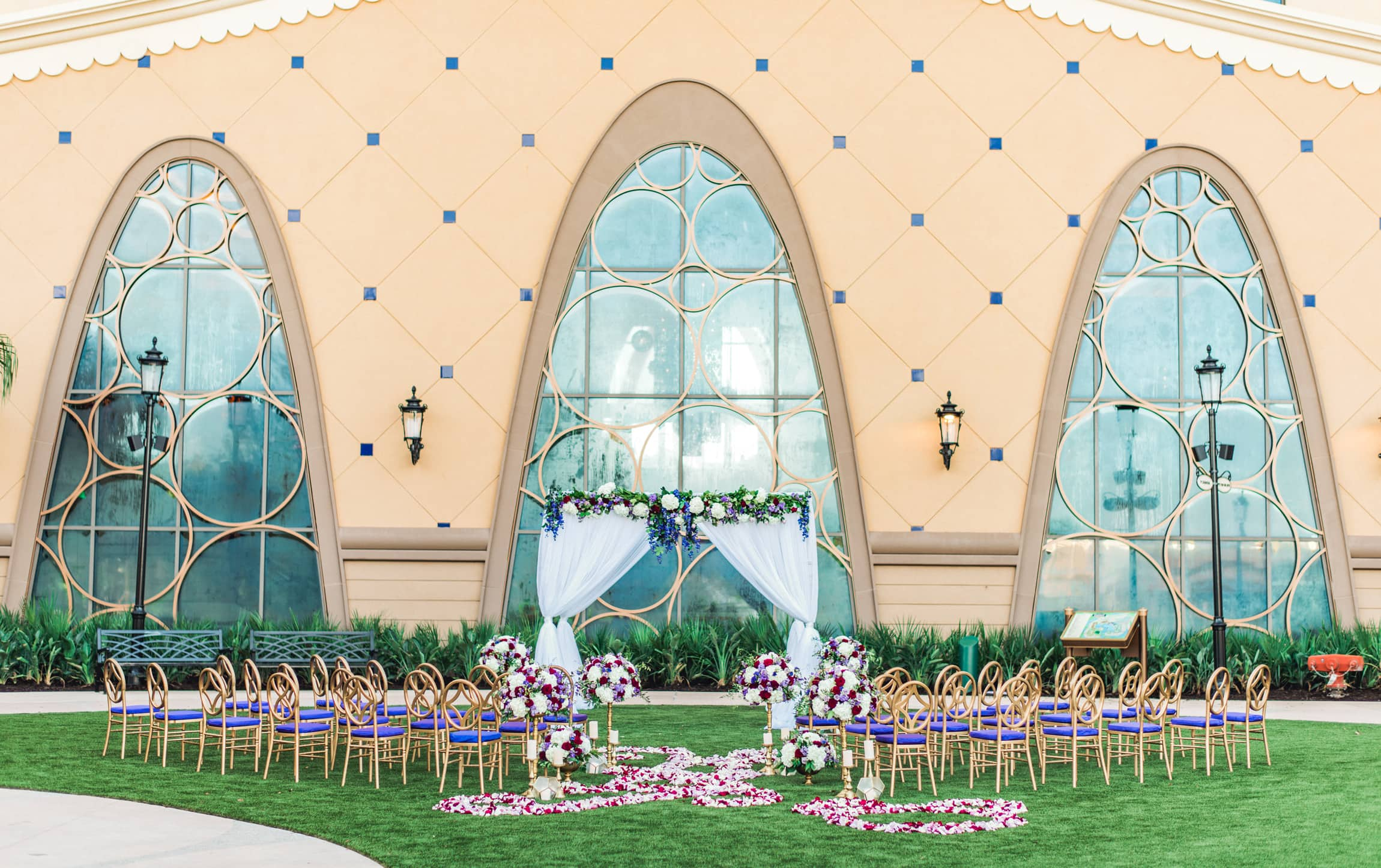 Chairs arranged on lawn facing a large building with many windows and floral decorations