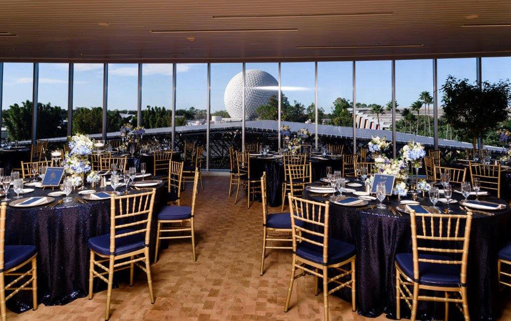 Circular tables arranged in a room with long clear windows showing a view of Spaceship Earth