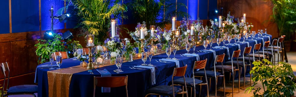 A long table holding several vases of flowers, candles, water glasses and champagne flutes