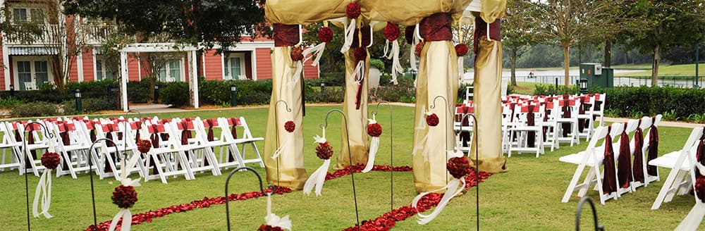 A gazebo decorated with roses and drapery on a lawn with aisles of chairs and a rose petal pathway