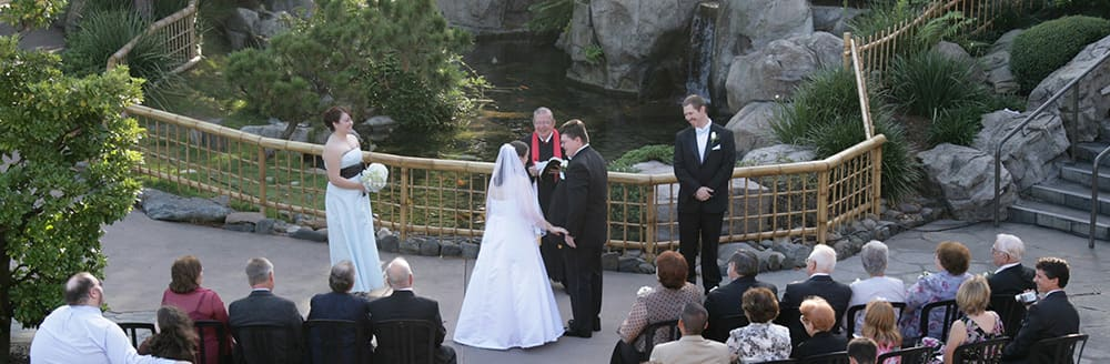 A couple marries in front of a koi pond with a priest and Guests watching