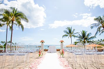 The 'AMA 'AMA Patio at Aulani Resort dressed for a wedding ceremony with chairs on either side of a flower lined aisle that leads to an altar with the ocean in the distance