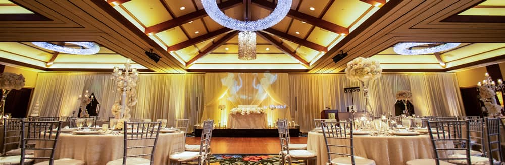 Round tables with elaborate floral centerpieces in a room with a dance floor
