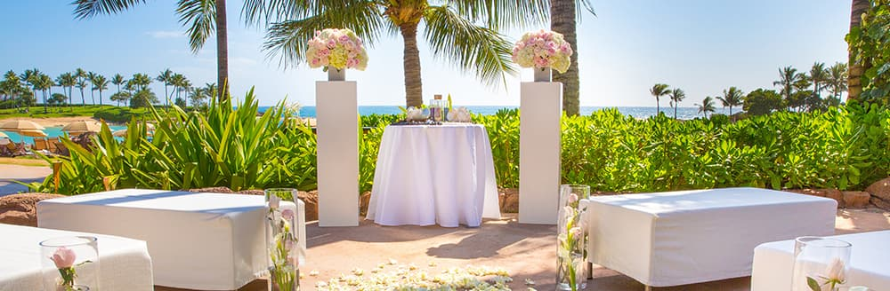 Large benches pointed towards an altar decorated with bouquets of flowers at a beach