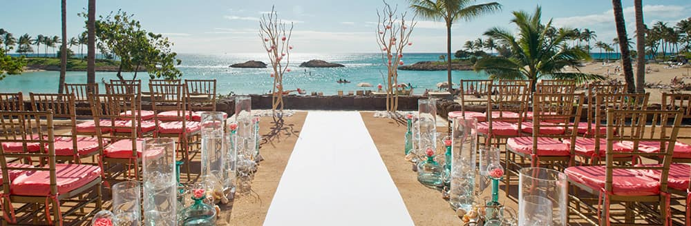 An outdoor wedding reception decorated with 2 trees at the front, aisles of chairs on either side, glass vases along the carpet path and a view of the ocean and palm trees