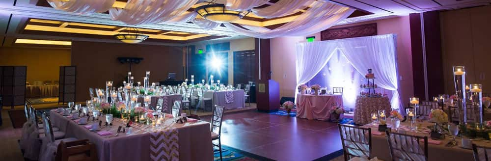 A softly glowing ballroom equipped with a dance floor and tables set for dinner