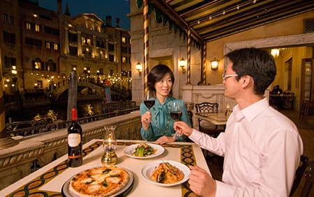 While seated at an outdoor dining table, a couple toasts each other before eating their meal