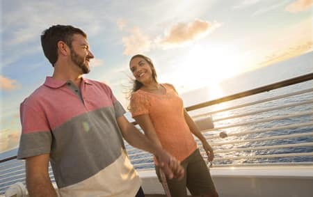 A man and a woman hold hands while strolling along the deck of a Disney Cruise Line ship