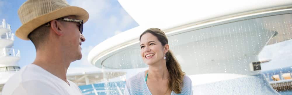 A man and a woman smile at each other on the deck of a Disney Cruise Line ship