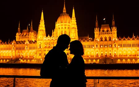 A silhouette of a man and a woman at night in front of a castle lit up by lights
