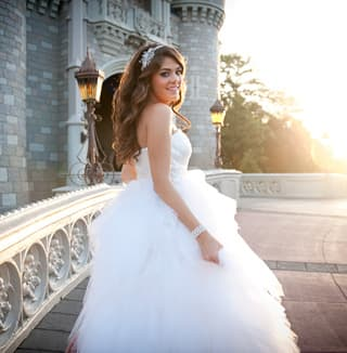 A bride standing in front of Cinderella Castle smiles while looking over her shoulder