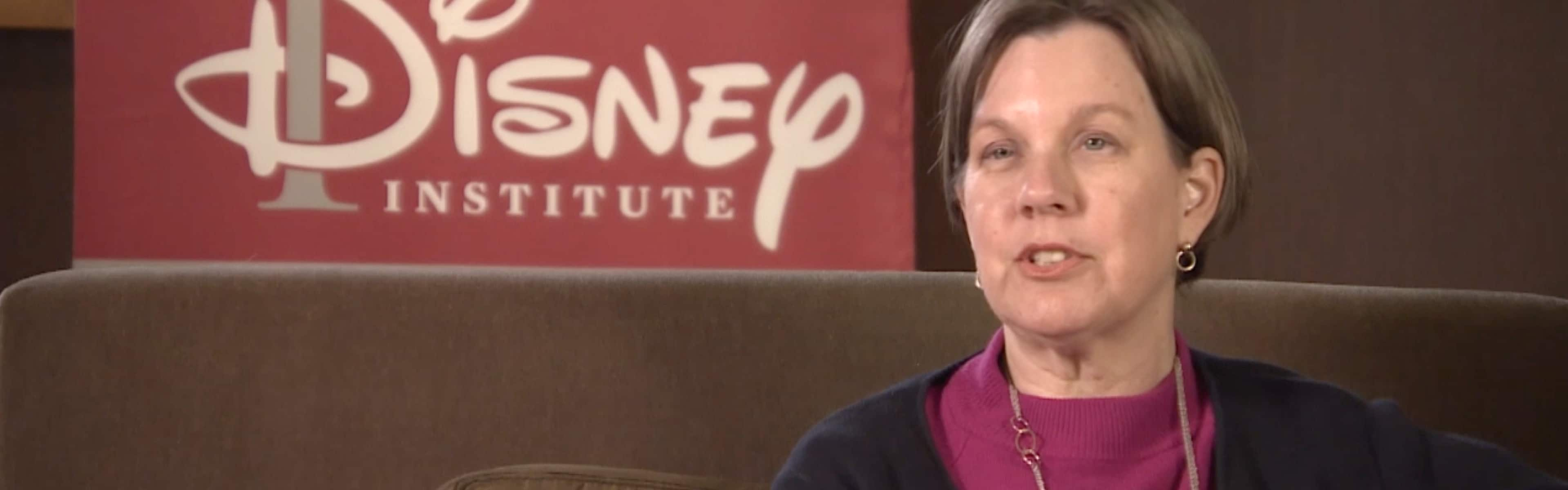 A talking woman seated on a couch in front of the Disney Institute sign