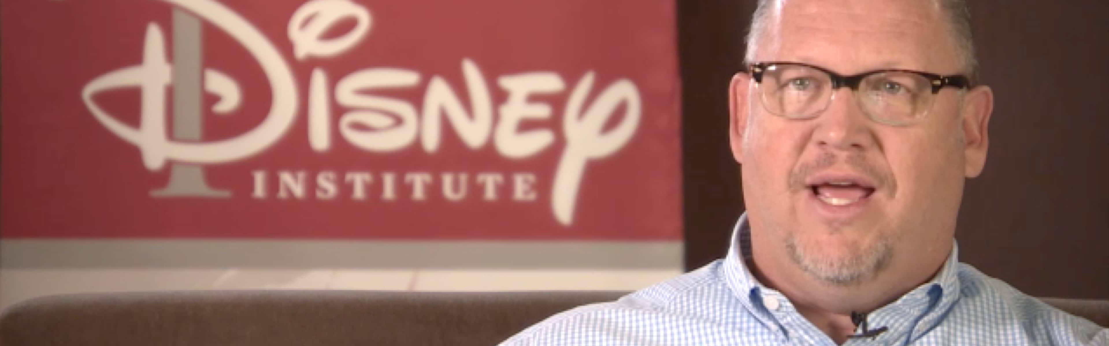 A talking man seated on a couch in front of the Disney Institute sign