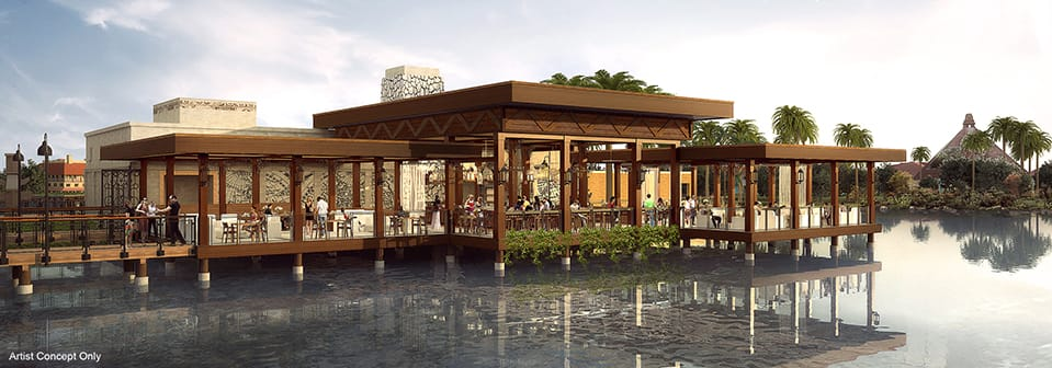 The outside of Villa del Lago located on the water with tables, chairs and palm trees surrounding the area