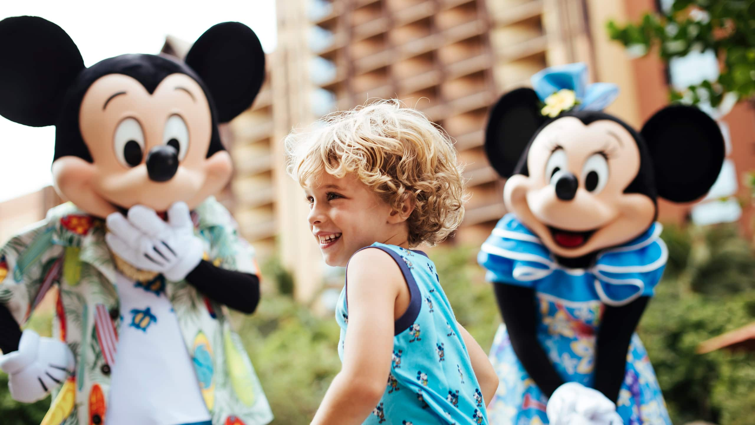 A young child smiling while standing near Mickey Mouse and Minnie Mouse