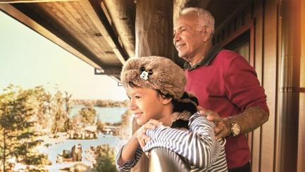 アライグマの毛皮の帽子をかぶり、父親と一緒に部屋のバルコニーから景色を見る少年