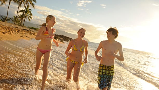 昼下がりの日差しの中、ビーチで走る 3 人のティーンエイジャー