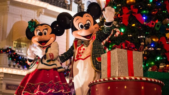 mickey and minnie mouse dressed in holiday attire standing beside a christmas tree and presents