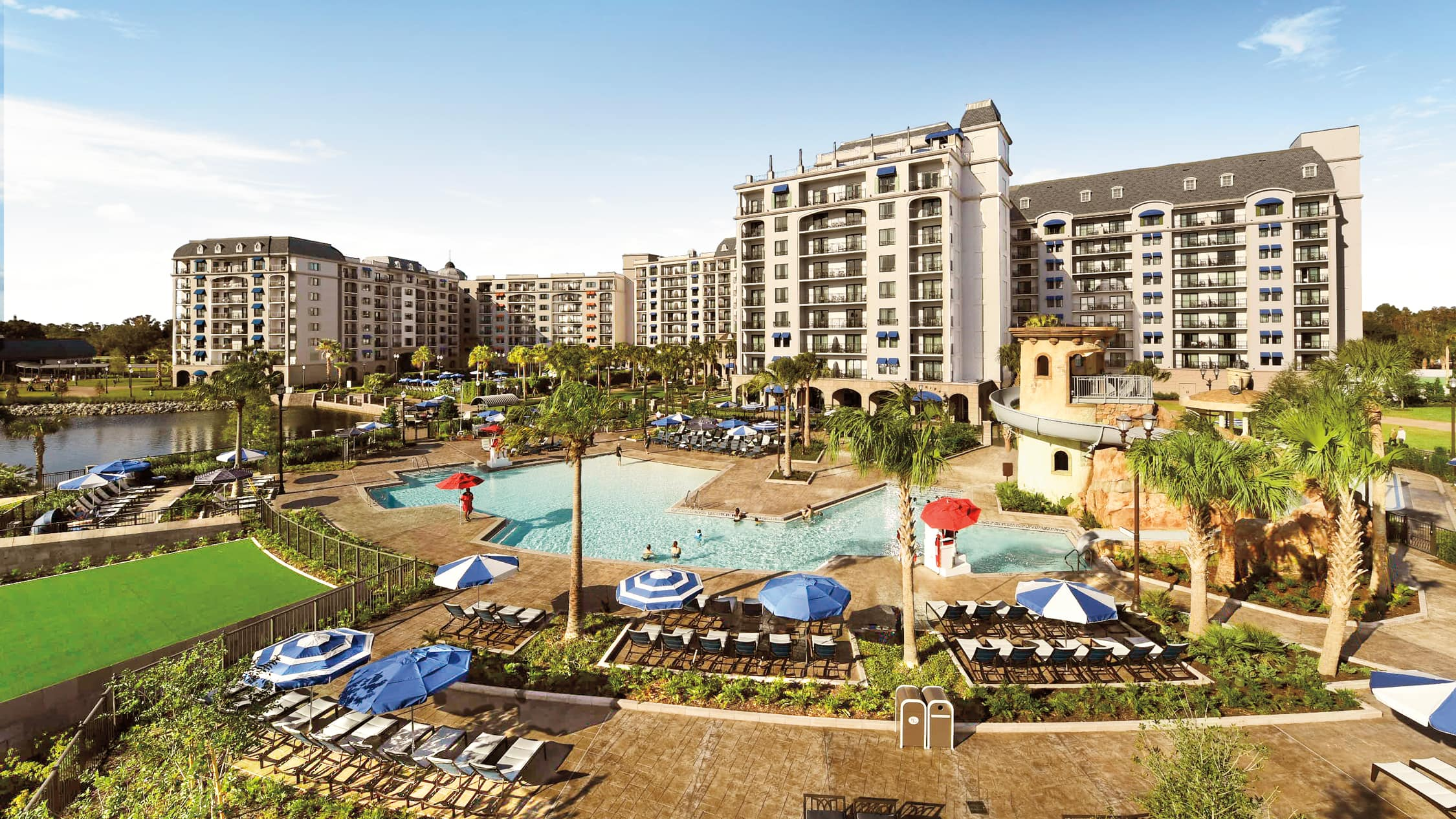 An outdoor pool with a waterslide, surrounded by lounge chairs, umbrellas and palm trees at Disney's Riviera Resort