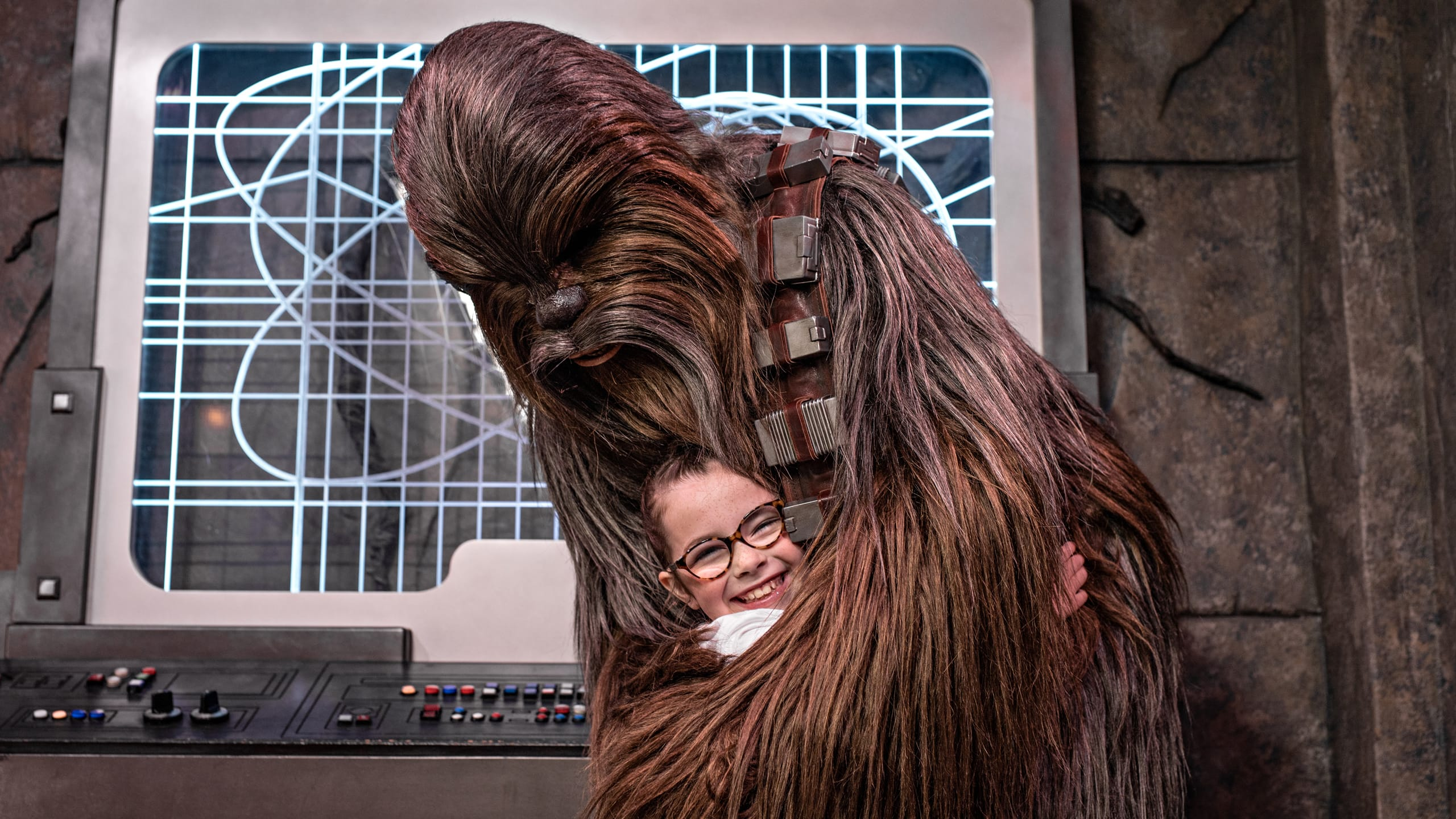 Chewbacca hugs a young girl in Star Wars Launch Bay