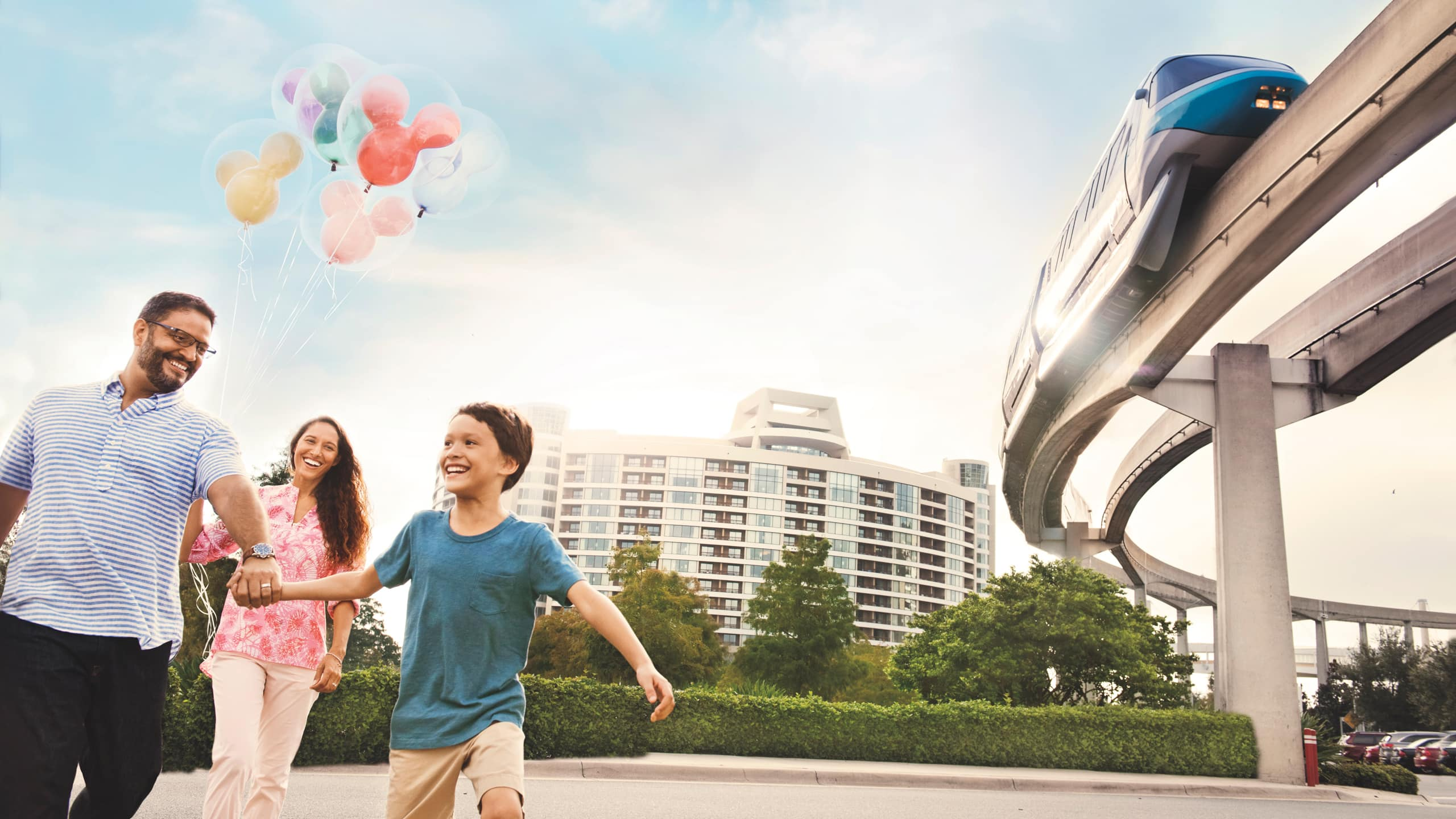 A man, woman and boy hold hands and carry Mickey Mouse balloons near a multi story hotel and a monorail