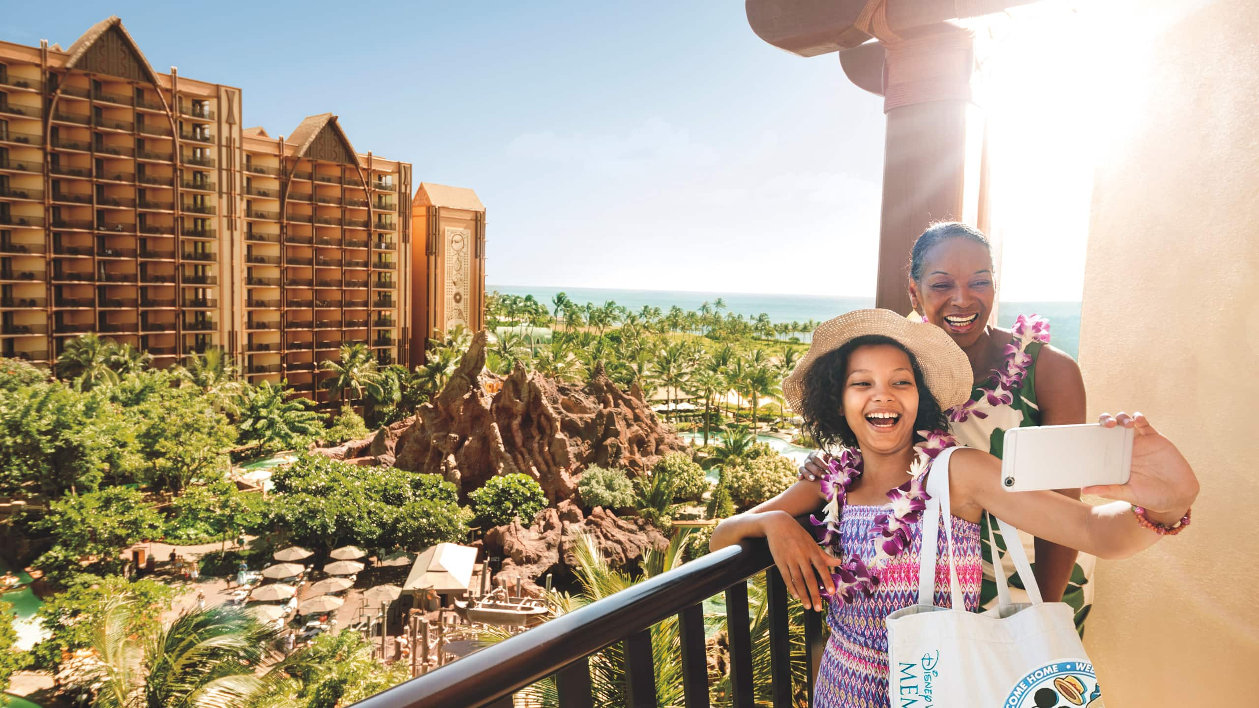 A mother and daughter take a selfie on the balcony of a hotel room room overlooking a Hawaiian landscape