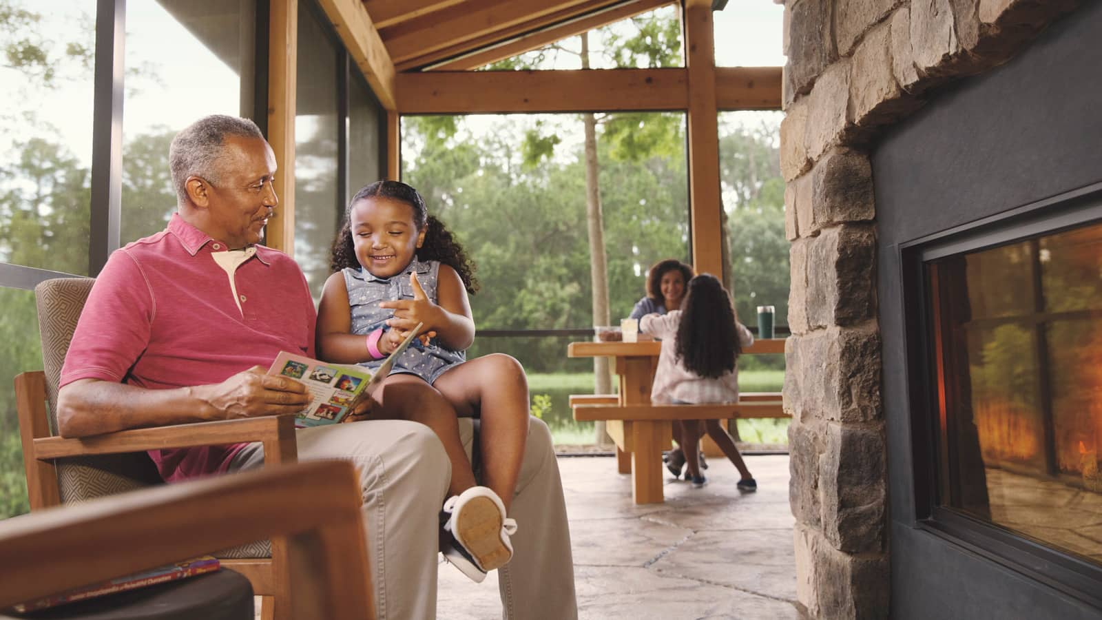 A man reads to a young girl in front of a fireplace and a woman and girl sit at a picnic table on a porch