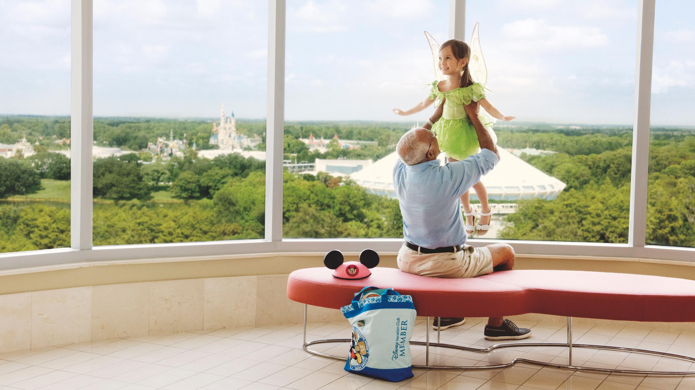 A man lifts his granddaughter near a window facing Cinderella Castle