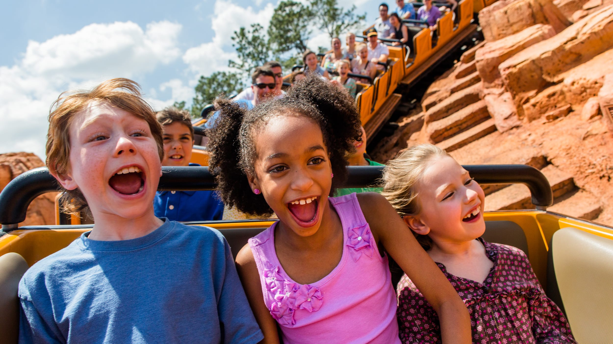3 children riding in the front row of the coaster on Big Thunder Mountain Railroad