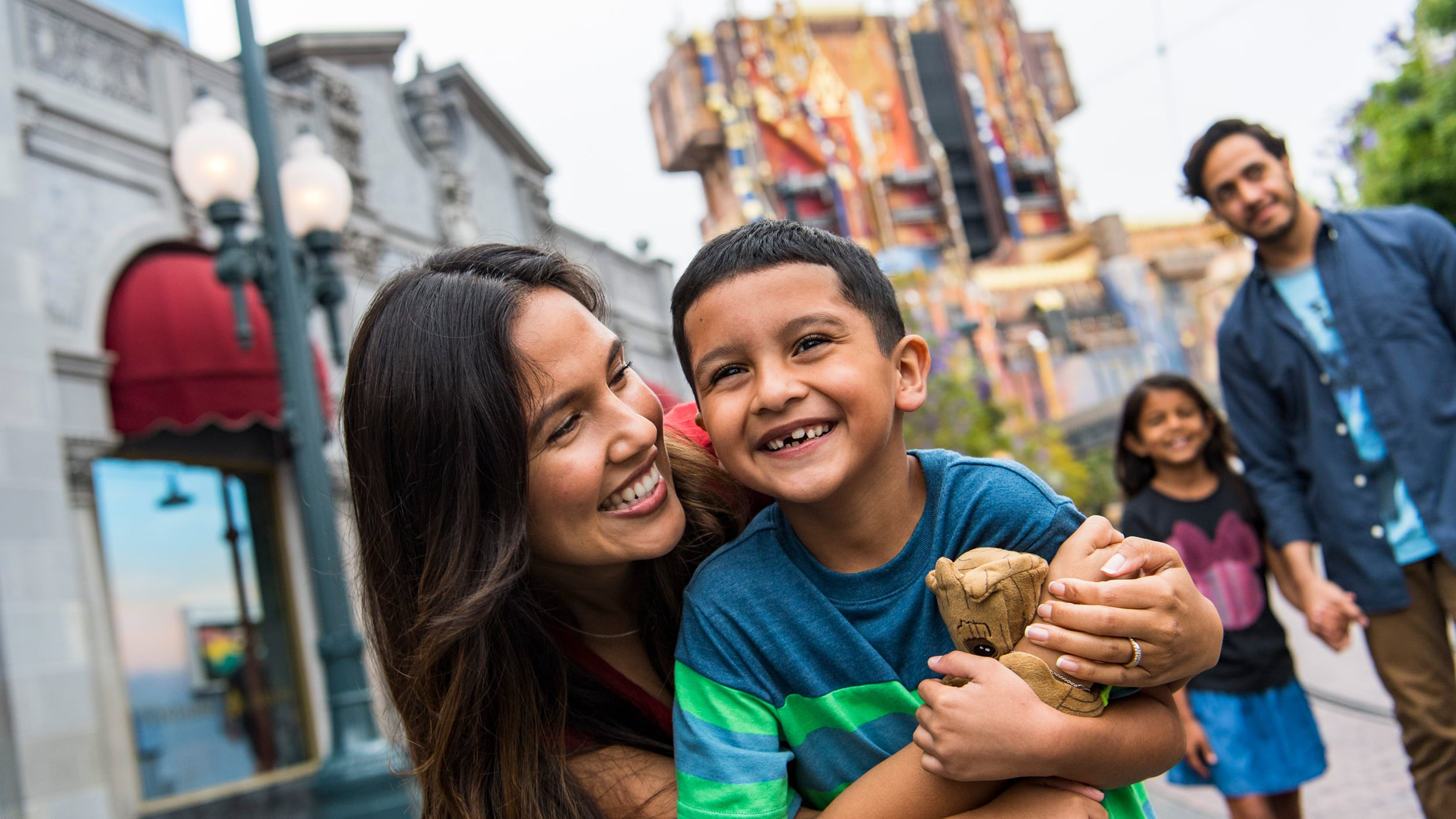 A mother, father, son and daughter walking outside at a theme park