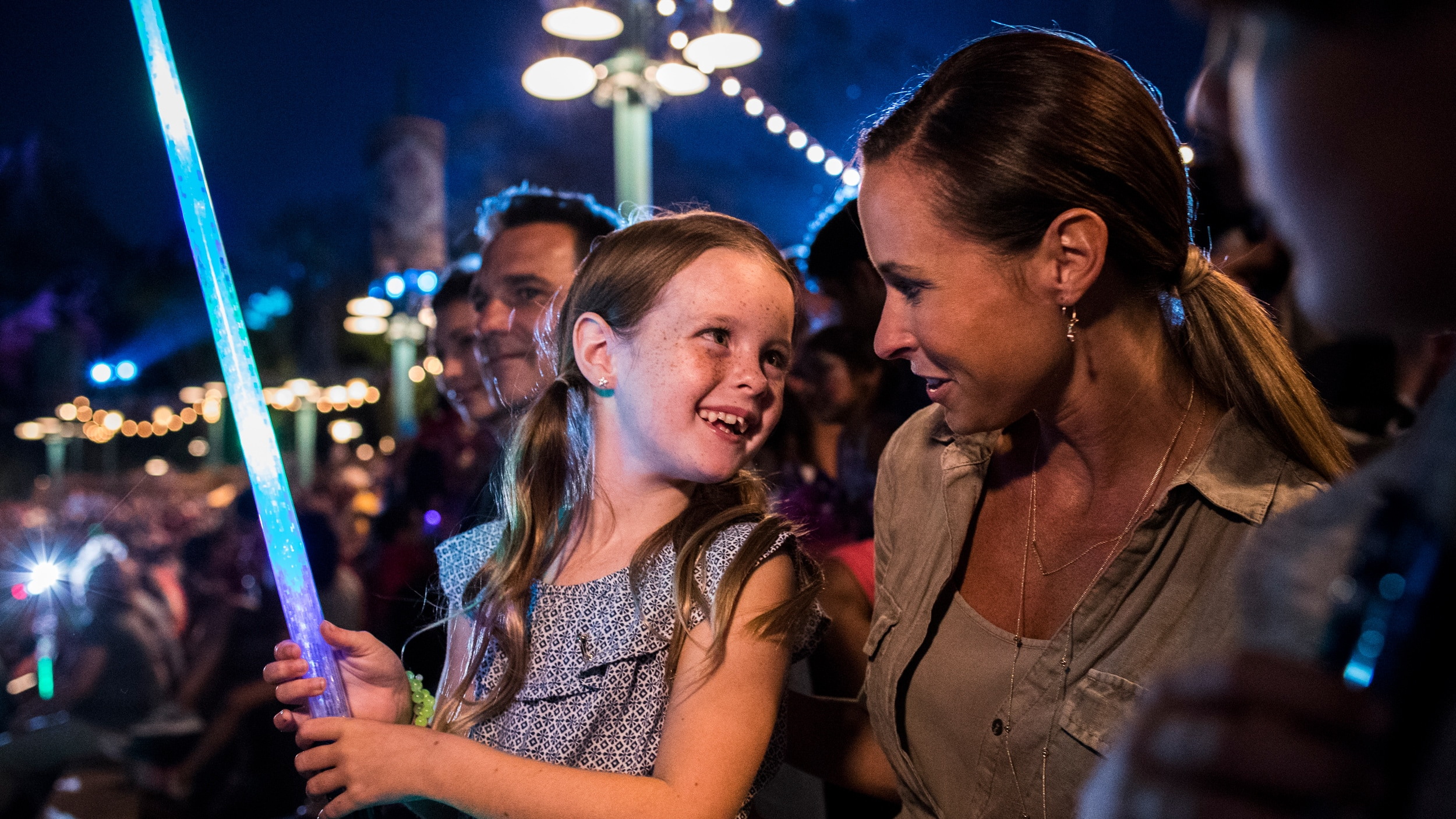 A young girl holding a lightsaber while smiling at her mother