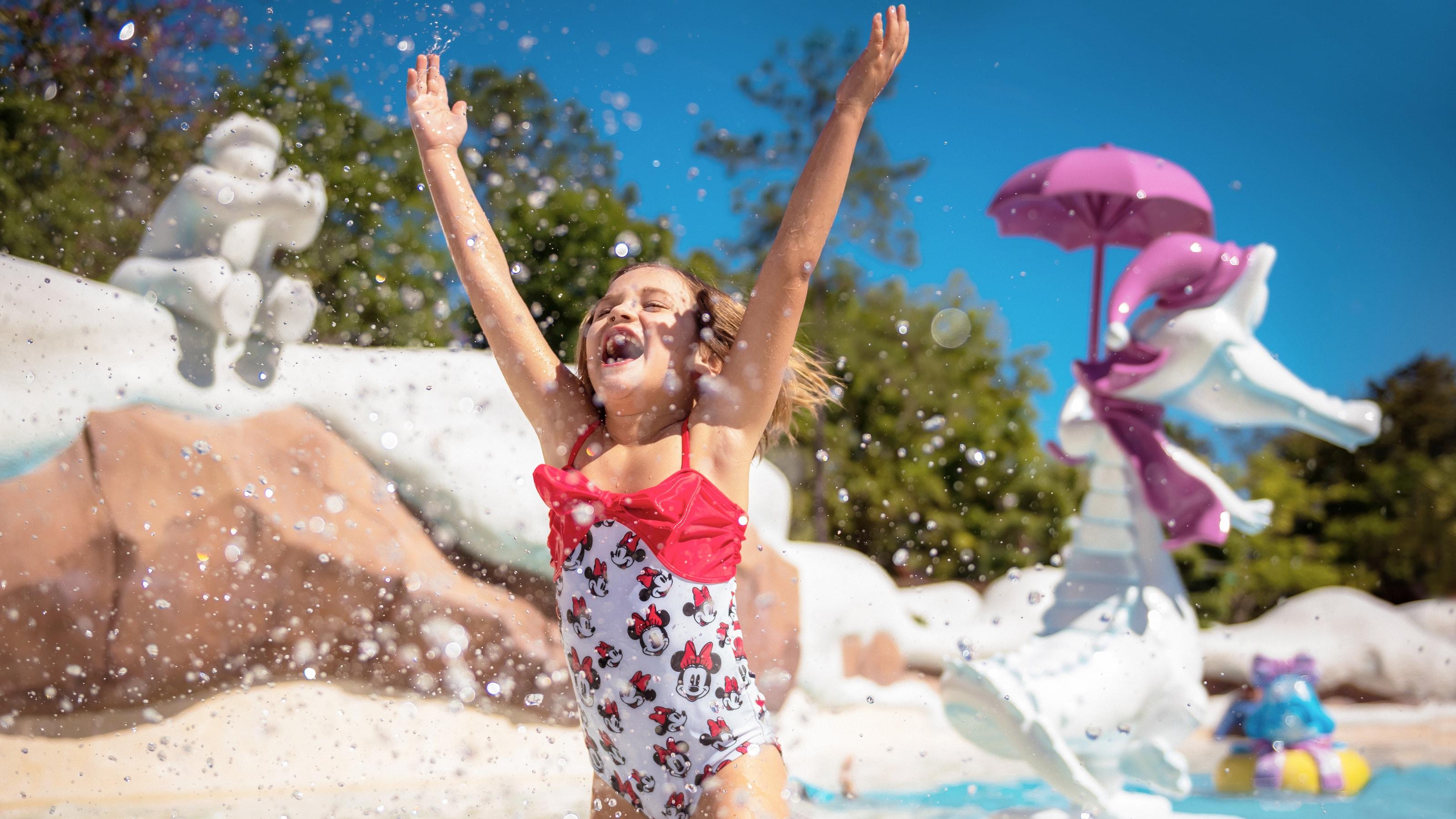 ミニーマウスの水着を着て、両手を挙げてプールで遊ぶ女の子