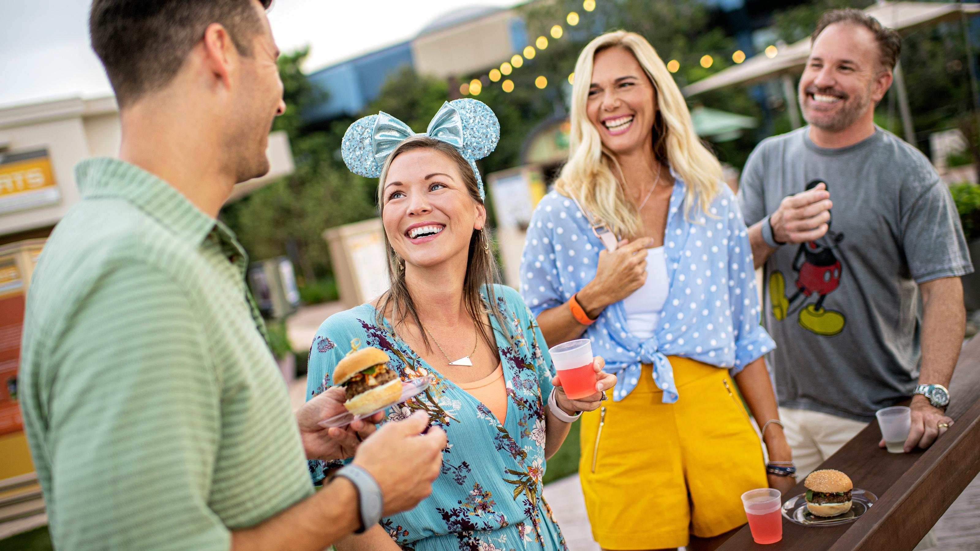 2 人の男性と 2 人の女性のグループ。1 人はミニーマウスのスパンコール耳付きカチューシャをつけて笑顔でスライダーを食べている