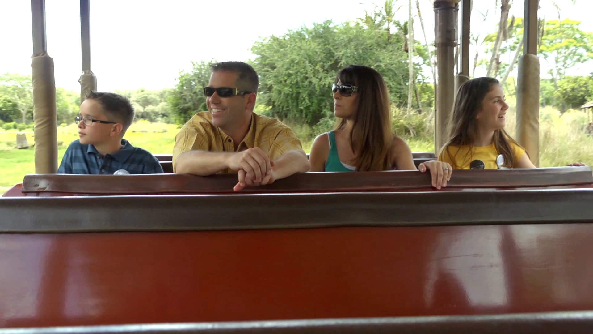 A family of 4 sits in the back row of an open air vehicle as they look out at a vast grassy area