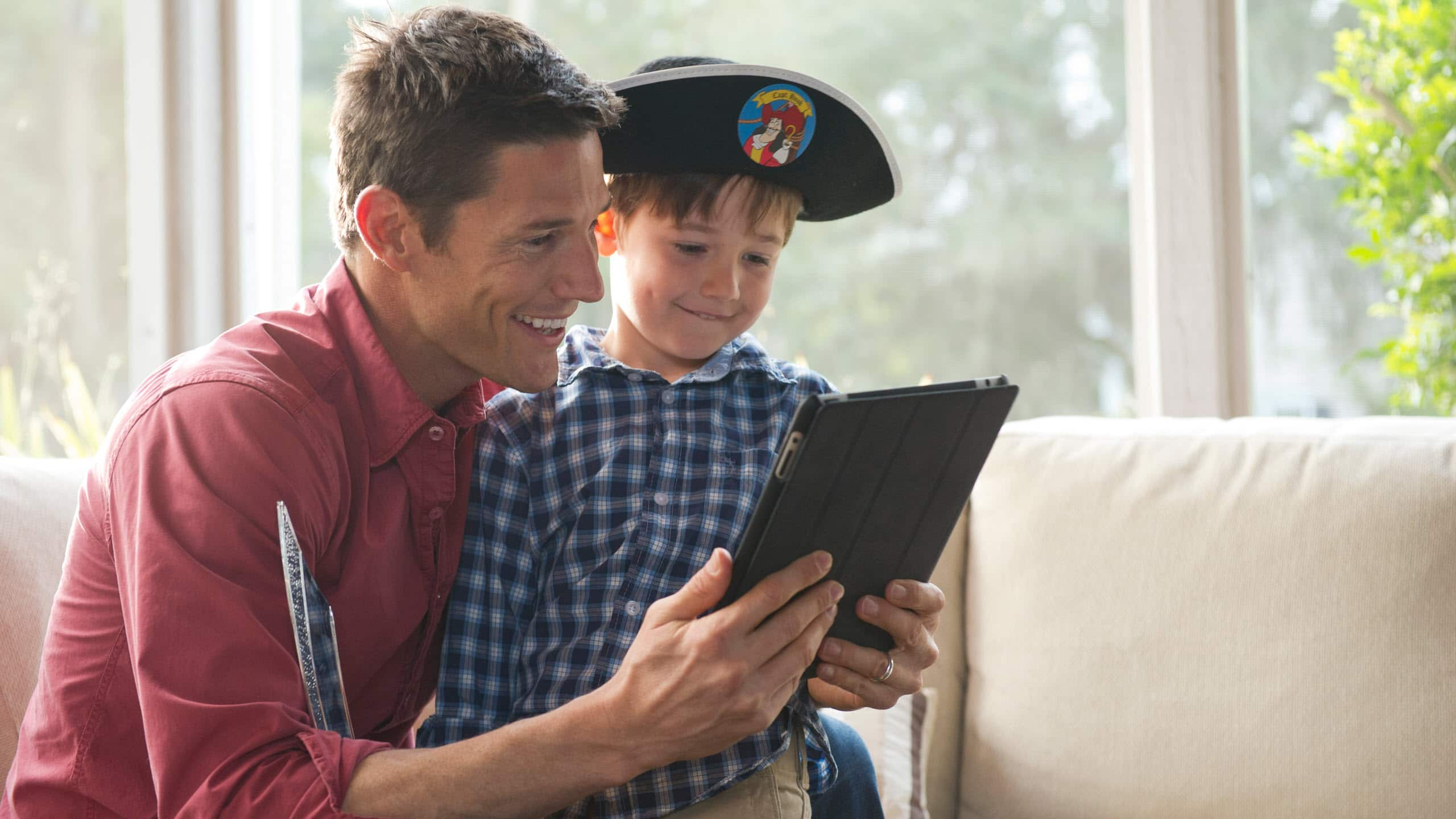 A boy wearing a pirate hat sitting with his father, reading a tablet device together