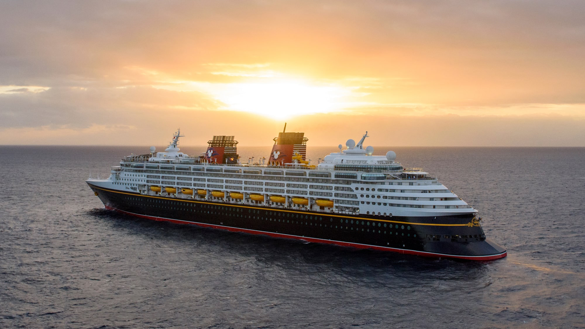 A Disney Cruise Line ship sailing in open waters at sunset
