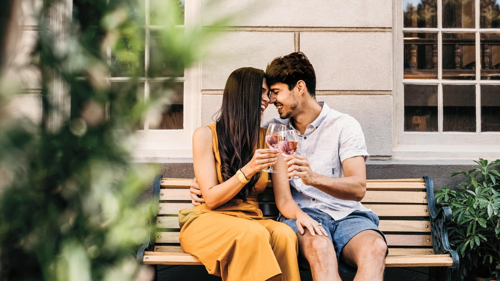 A couple embraces on a bench as they toast with wine