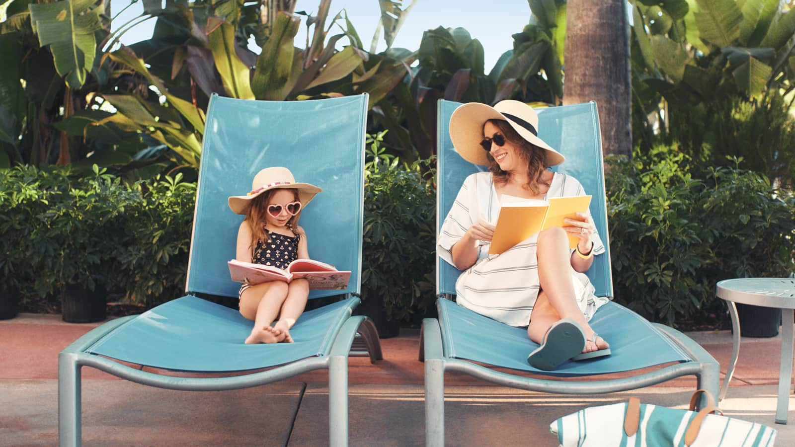 A mother and a daughter wearing pool attire read in lounge chairs in front of dense foliage