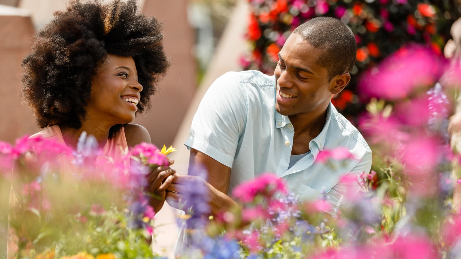A man and woman surrounded by flowers