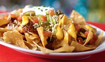 Nachos with chili, shredded lettuce, jalapeños, diced tomatoes and sour cream