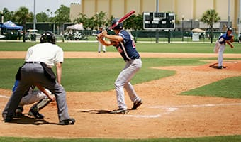 An umpire watches as a batter prepares to hit a baseball thrown by a pitcher