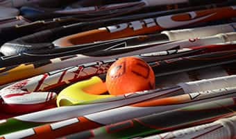 A field hockey ball sits on the ground among several field hockey sticks