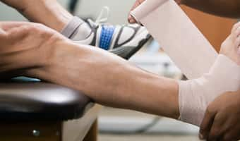 An athletic trainer wraps an athlete's ankle and foot