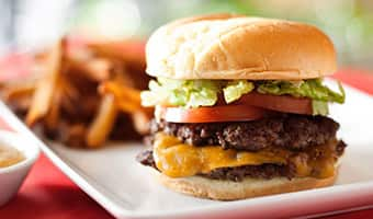 A cheeseburger with 2 patties, lettuce and tomato and fries