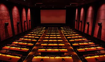Stadium seats with tables inside at a movie theatre at AMC Disney Springs 24 Theatres