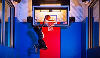 A teenage basketball player is mid-jump holding a basketball above the rim of a basketball backboard with the NBA logo and an American flag on it