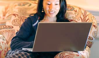 A woman sits on a comfortable sofa and surfs the net on her laptop