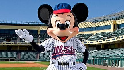 Mickey Mouse vestido con uniforme de béisbol parado en uno de los campos de béisbol