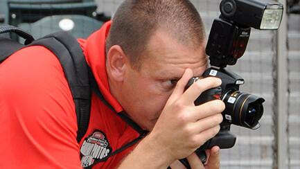 A photographer looking through the viewfinder of his camera