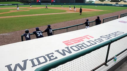 "Several baseball players on a field, by a banner that reads ""ESPN Wide World of Sports Complex"""